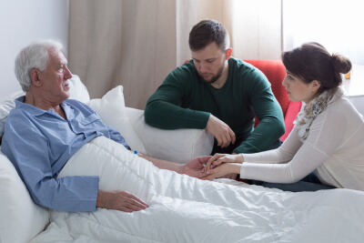 couple and elder man in bed talking